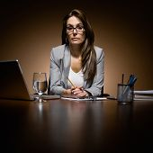 Serious, unhappy businesswoman working late at desk with laptop and paperwork
