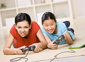 stock photo of puberty  - Determined friends having fun using video game controllers to play exciting video game - JPG