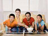 Amigos bebiendo refrescos y comer disfrutando ver televisión de palomitas de maíz