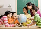 stock photo of pre-teen boy  - Teacher and students viewing globe in geography classroom - JPG
