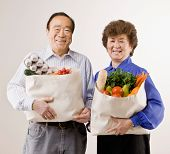 Confident couple holding grocery bag full of fresh wholesome fruits and vegetables