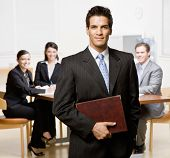 Confident businessman with notebook and co-workers in conference room