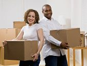 Happy couple moving into new home carrying cardboard boxes