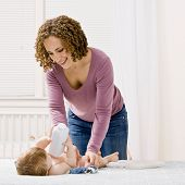 stock photo of diaper change  - Devoted mother change her son - JPG