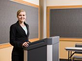 Businesswoman standing behind podium preparing to give presentation in conference room