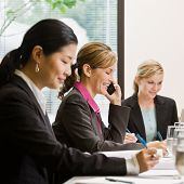 Busy female co-workers meeting at table in conference room