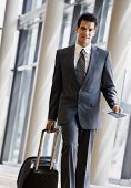 Business traveler pulling suitcase and holding passport and airline ticket