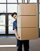 Delivery man in uniform carefully carrying stack of cardboard boxes