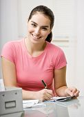 Responsible woman writing checks in checkbook to pay monthly bills