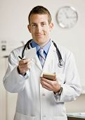 Confident doctor in lab coat and stethoscope handing prescription from pad in doctor?s office