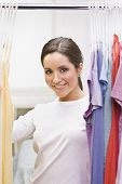 A beautiful brunette looking through clothing in a closet.  She is smiling at the camera. Vertically