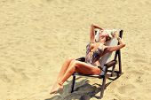 Young beautiful blond woman on sunbed on the beach