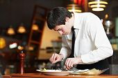 man waiter in uniform preparing fish food on plates at restaurant