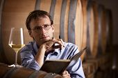 Winemaker contemplating over white wine creation and taking notes in wine cellar with barrels in background.
