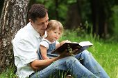 young father with his daughter read the Bible in nature