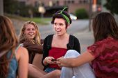 stock photo of bff  - Hispanic female teenager with friends sitting on the ground - JPG