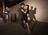 stock photo of debonair  - Bellows musician with Tango dancers in spotlight - JPG
