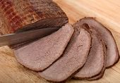 stock photo of pot roast  - A beef round joint being sliced for serving after being braised  - JPG