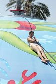pic of inflatable slide  - Woman is sliding on wet bubble game pool in water park Rhodes - JPG