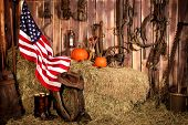 foto of horse plowing  - American flag draped over hay bales in a barn filled with old tools and plow horse equipment - JPG
