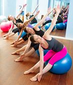 Grupo de mulheres de aeróbica de Pilates com bola de estabilidade em uma linha no ginásio do espelho