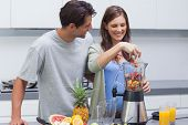 Couple putting various fruits into blender