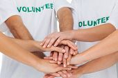 Group of volunteers piling up their hands together