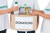 Group of volunteers putting food in donation box on white background