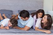 stock photo of tickling  - Parents tickling their children on bed at home - JPG
