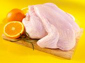 pic of charcuterie  - Fresh raw chicken on cutting board with oranges - JPG