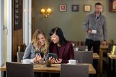 Female friends using digital tablets while man standing in background at cafe