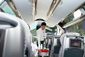 ROAD FROM BURSA TO ISTANBUL, TURKEY - AUGUST 20: Steward serves drinks to passengers during the trav
