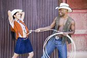 picture of lasso  - Young man in cowboy outfit lassoing his girlfriend - JPG