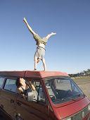 Man macht einen Handstand auf Autodach