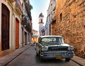 HAVANA, CUBA-MAY 14: Street scene with an old rusty american car on May 14, 2013 in Havana.These cla