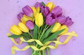 Yellow and purple tulip flower bouquet with ribbon over mottled lilac background.