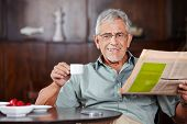 Happy senior man sitting with coffee and newspaper in a caf�?�?�?�©