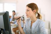 stock photo of electronic cigarette  - Girl smoking with electronic cigarette in office - JPG