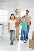 Familia con cajas en nuevo hogar sonriendo