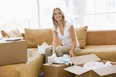 Woman Unpacking Boxes In New Home Smiling