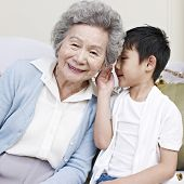 stock photo of grandma  - little asian boy whispering and telling grandma a secret - JPG