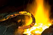picture of blacksmith shop  - The blacksmith forges a horseshoe in his workshop - JPG
