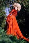 Fantasy. Artistic Stylized Woman In Trendy Red Dress And Big Frizzy Wig