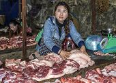 Female Butcher Grabbing Pieces Of Fat From A Table Full Of Cut Meat On Market.