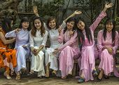 Seven Joyful Female University Seniors Dressed In Ao Dai.