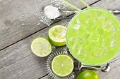foto of lime  - Classic margarita cocktail with salty rim on wooden table with limes and drink utensils - JPG