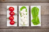 Tomatoes, mozzarella and green salad leaves on wooden table background