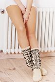 Long smooth beautiful legs with high warm socks over wooden floor.