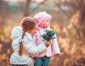 happy little girl and her sister holding a bouquet of flowers