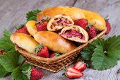 Slice of fresh baked pasties with strawberries in a basket close-up